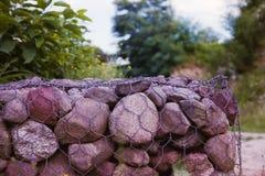 A parede com pedras entrelaçou-se com uma rede do metal foto de stock royalty free