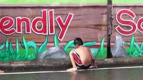 A parede concreta pintada pintura mural da escola é um lugar onde um menino aprecie o banho da chuva vídeos de arquivo