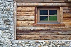Parede da cabana rústica de madeira com fundação da pedra da janela e de campo Fotos de Stock Royalty Free