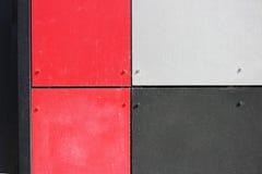 A parede da casa, aparada com os painéis coloridos, pintados em cores brilhantes Cinza, preto e vermelho Imagens de Stock Royalty Free