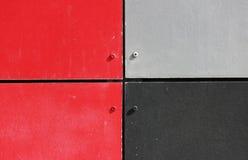 A parede da casa, aparada com os painéis coloridos, pintados em cores brilhantes Cinza, preto e vermelho Fotografia de Stock