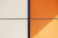 A parede da casa, aparada com os painéis coloridos, pintados em cores brilhantes Laranja e bege Foto de Stock Royalty Free