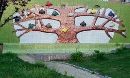 A parede da casa, decorada com uma imagem decorativa de uma árvore dourada com muitos pássaros coloridos nela Imagens de Stock Royalty Free