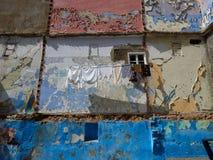 A parede da casa velha, decorada em quadrados coloridos de cores azuis, brancas, cor-de-rosa e marrons, uma janela de madeira bra Foto de Stock Royalty Free