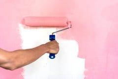 Parede da pintura da mão com rolo de pintura foto de stock