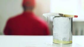 Parede da pintura do trabalhador com rolo escova de pintura do gotejamento com cubeta da cor filme