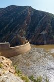 A parede da represa construída ao lado das montanhas fotos de stock