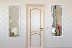 Parede da sala de visitas com uma porta e as duas inserções simétricas dos espelhos fotos de stock royalty free