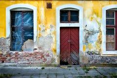 Parede danificada velha com janelas barradas e uma porta 1 imagem de stock
