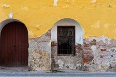 Parede danificada velha com janelas barradas e uma porta fotos de stock royalty free