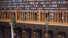 A parede das estantes na biblioteca vídeos de arquivo