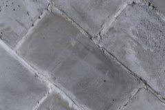 A parede das paredes velhas da cidade do fragmento diagonal dos blocos concretos, cinzentos, porosos imagens de stock royalty free