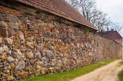 A parede de alvenaria do solar velho Shlokenbek das pedras em Letónia fotografia de stock