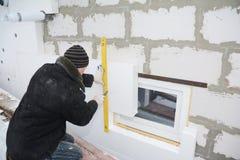 A parede de isolamento da casa do contratante de construção com isolação do isopor cobre na área de problema em torno da janela foto de stock