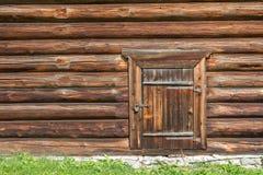 Parede de madeira velha da casa de log com porta fechado e cadeado nele Foto de Stock