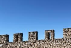 Parede de pedra antiga com ameias, perspectiva Fotos de Stock Royalty Free