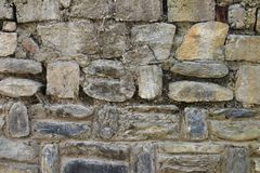 Parede de pedra antiga velha feita dos pedregulhos do formulário natural, prendidos com textura da argila, a bege e a amarelada d Fotografia de Stock