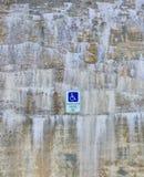 Parede de pedra bonita com depósitos minerais e fundo deficiente do sinal do estacionamento Imagens de Stock Royalty Free