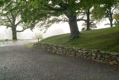 Parede de pedra cedo empilhada ao longo de uma estrada Imagens de Stock Royalty Free
