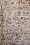 Parede de pedra com pedras numeradas Números vermelhos de dois dígitos nas pedras Restauração da parede foto de stock