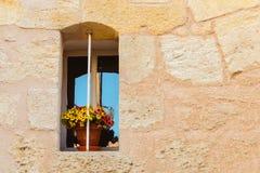 Parede de pedra com uma janela velha e um potenciômetro de flor amarelo fotos de stock royalty free