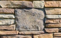Parede de pedra da rocha com a grande pedra do centro para o fundo rústico fotos de stock