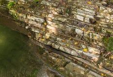Parede de pedra de uma rocha coberta com o musgo no pé de um lago transparente Fotografia de Stock