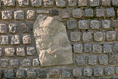 Parede de pedra decorada com pedras do granito com uma grande pedra no centro fotos de stock royalty free