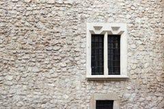 Parede de pedra e cimento velhos com janela velha Fundo de pedra Parede de pedra de Krakow Chapas para assar nas janelas Construç fotografia de stock