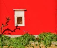 Parede de pedra vermelha com a janela branca sob o sol imagens de stock