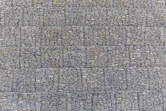 A parede de pedras do rio embalou em uma grade do metal Fotografia de Stock Royalty Free