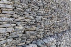 A parede de pedras do rio embalou em uma grade do metal Imagem de Stock