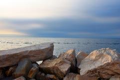 Parede de pedras grande perto do mar no por do sol Imagem de Stock