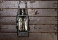 Parede de placas idosas marrons com uma lanterna de querosene velha imagens de stock royalty free