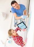 Parede de sorriso da pintura dos pares em casa Fotos de Stock Royalty Free