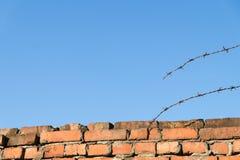 Parede de tijolo, arame farpado rasgado e céu azul fotos de stock