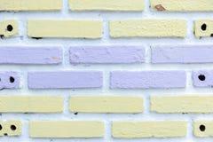 Parede de tijolo branca pintada com textura roxa e amarela macia do fundo imagem de stock