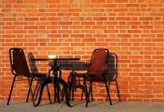 Parede de tijolo com cadeiras de couro e uma mesa de centro Fotos de Stock Royalty Free