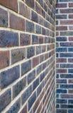 Parede de tijolo com os tijolos roxos e vermelhos e apontar branco imagem de stock royalty free