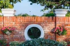 Parede de tijolo de jardinagem com potenciômetros de flor Imagem de Stock Royalty Free