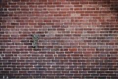 Parede de tijolo escura com rolado acima da suspensão Chain Foto de Stock