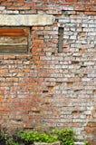 A parede de tijolo gasto velha com embarcado acima da janela Imagem de Stock