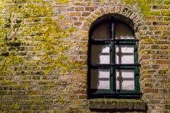 Parede de tijolo musgoso com um quadro de janela de madeira velho atrás das barras, fundo histórico da arquitetura foto de stock