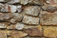 Parede de tijolo de pedra no meio da argila, decoração mergulhada da pilha, estilo retro exterior da luz solar Imagens de Stock
