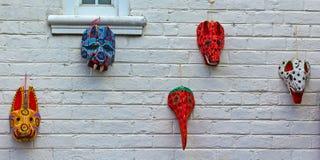Parede de tijolo pintada com máscaras de madeira da Guatemala Imagens de Stock Royalty Free