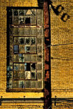 Parede de tijolo, polo de serviço público e janela quebrada Foto de Stock