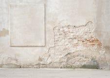 Parede de tijolo rachada abandonada com um quadro do estuque Fotos de Stock Royalty Free