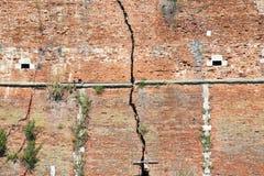 Parede de tijolo rachada - quebra profunda em uma parede de tijolo Fotos de Stock