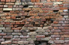 Parede de tijolo resistida velha feita de tijolos multi-coloridos Fotografia de Stock Royalty Free