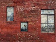 Parede de tijolo velha mesma com necessidade de apontar o reparo com as três janelas diferentes, fundo arquitetónico fotografia de stock royalty free